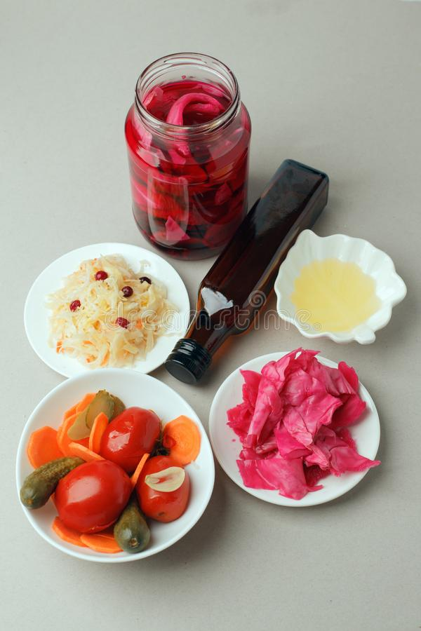 Fermented vegetables on plate on gray background: sauerkraut, pickled cabbage with beetroot, pickled cucumbers, carrots and royalty free stock images