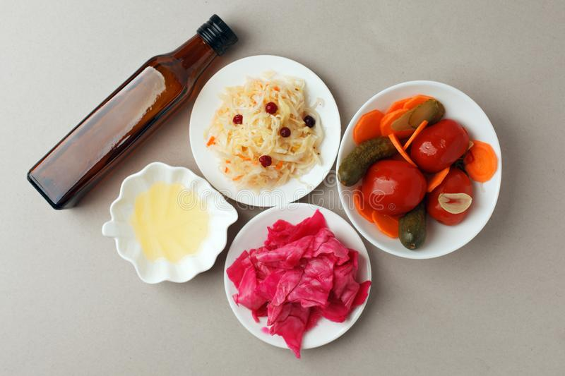 Fermented vegetables on plate on gray background: sauerkraut, pickled cabbage with beetroot, pickled cucumbers, carrots and stock image