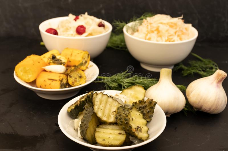 Fermented vegetables in two white bowls and two white plates stock photography