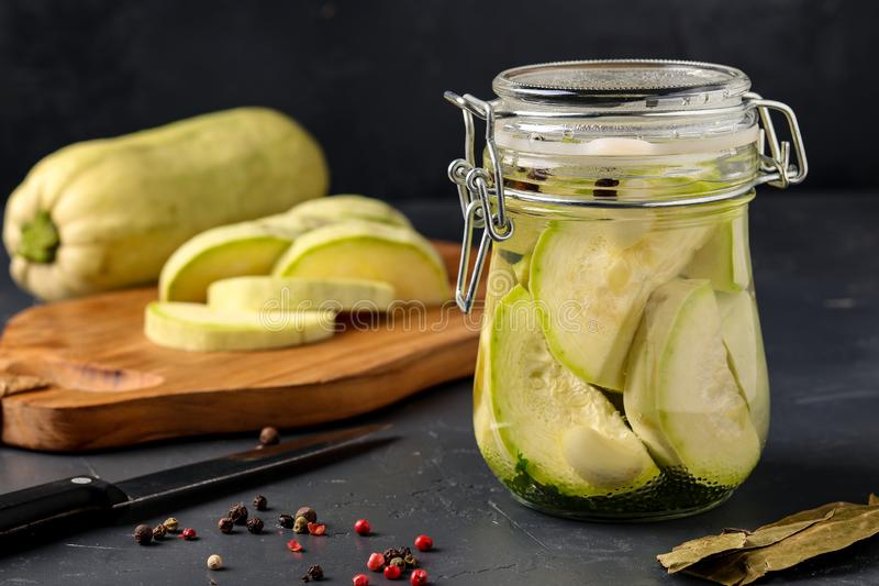 Fermented zucchini in jar on a dark background, Harvesting vegetables for healthy food, copy space, horizontal orientation. Fermented zucchini in jar on a dark royalty free stock photos