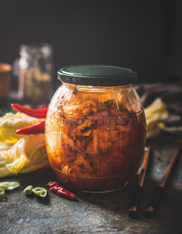 Fermenterade livsmedel Homemade kinesisk kål i hett sås, kimchi i glasburk i mörk, rustig bakgrund Begreppet livsmedel arkivbild