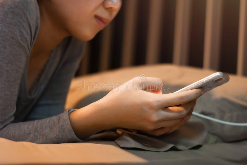 Fermer une jeune femme tenant et utilisant son téléphone portable couché sur le lit à la maison images stock