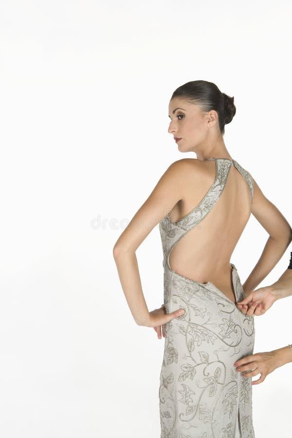 Fermeture éclair de attente de belle femme à faire sur la robe sans dos photos libres de droits