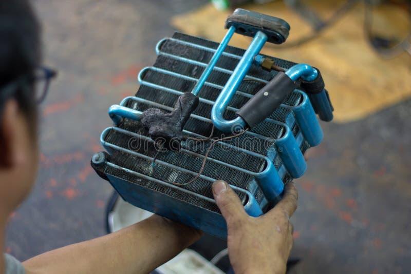 Fermeture de l'évaporateur de l'air conditionné de la voiture Ouvrier mécanicien auto réparant l'état de l'air dans le garage de  image libre de droits