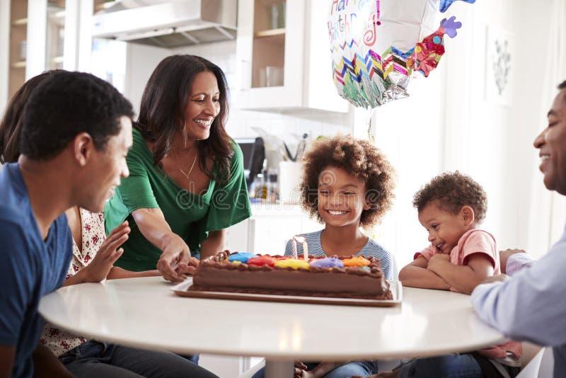 Fermeture de la famille de trois générations assise à la table de la cuisine pour célébrer l'anniversaire de la fille ? avant l'a image libre de droits