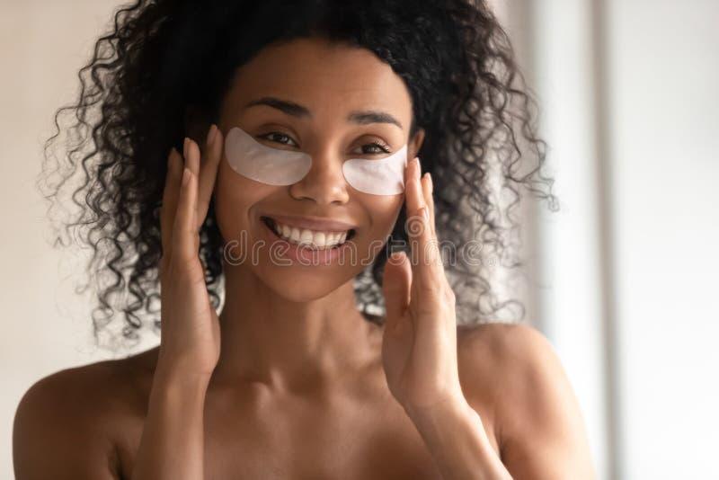 Fermeture de la femme biraciale souriante en appliquant des patchs sous les yeux photos stock