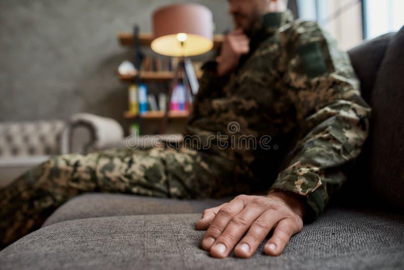 Fermeture de la main d'un militaire en camouflage assis sur le canapé pendant la séance de thérapie Soldat souffrant photos stock