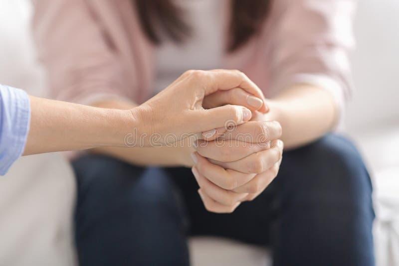 Fermeture de la thérapeute touchant les mains des patientes photographie stock libre de droits