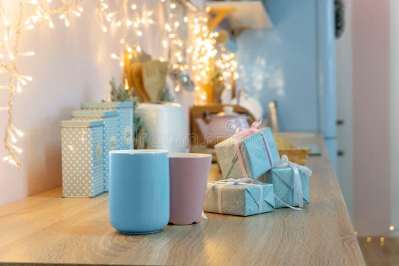 Fermeture de tasses roses et bleues et cadeaux emballés sur le comptoir Cuisine blanche et bleue rose pour les vacances, lumière  image libre de droits