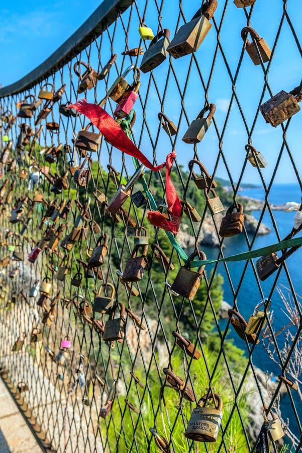 Fermeture des serrures sur la grille sur le fond de la mer bleue et un symbole de fidélité et d'amour éternel photographie stock libre de droits