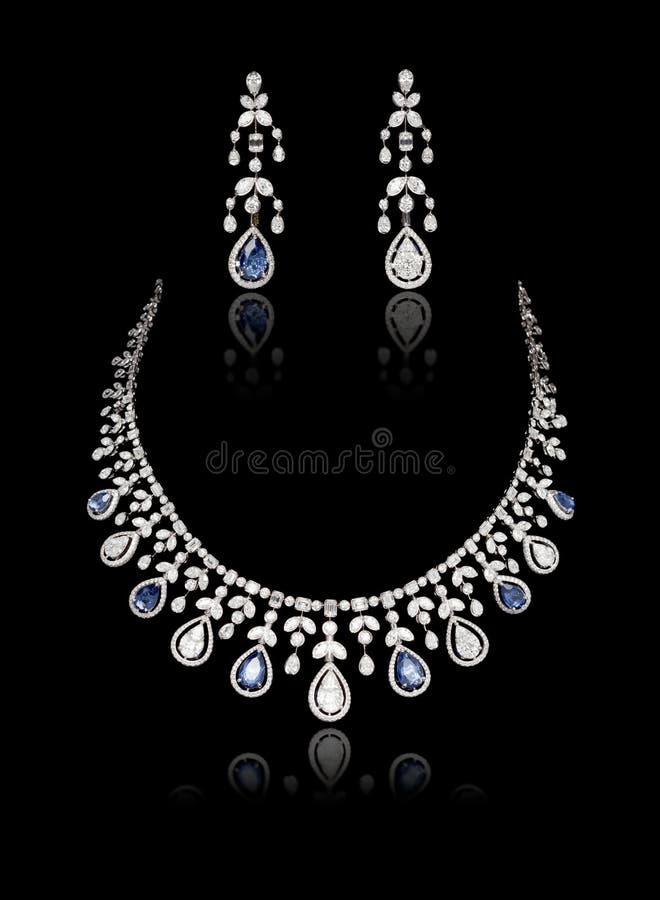 Fermeture du collier de diamant sur lequel est fixé l'oreille au diamant isolé sur le noir photographie stock libre de droits