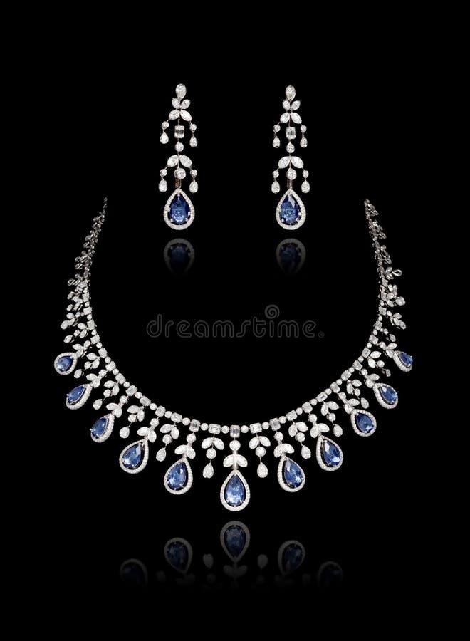 Fermeture du collier de diamant sur lequel est fixé l'oreille au diamant isolé sur le noir images stock