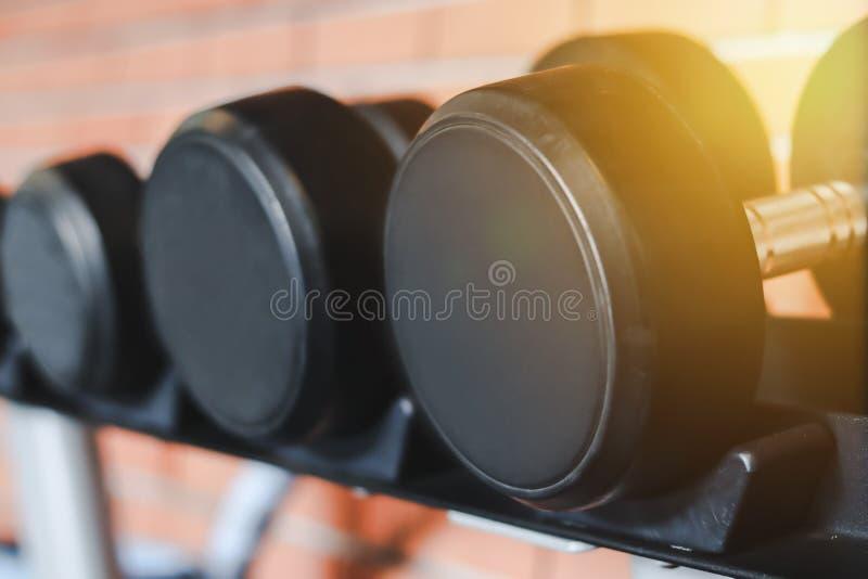 Fermez beaucoup d'haltères en métal sur le support dans la chambre de forme physique avec le mur de briques Bacckground Mat?riel  photo libre de droits