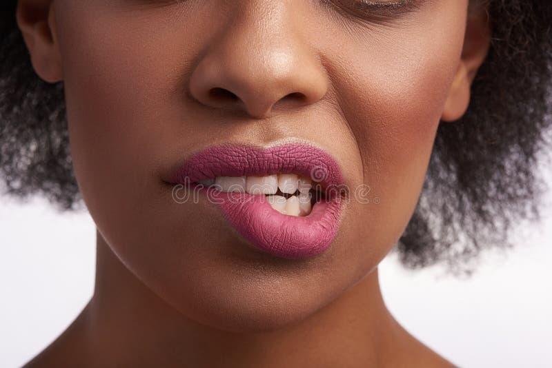 Fermez de la morsure femelle ethnique sensuelle sa lèvre photo stock