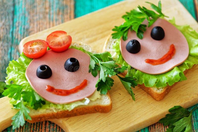 Fermez des sandwichs drôles les visages d'une fille et d'un garçon pour un repas scolaire Concept de nouveau ? l'?cole photographie stock libre de droits