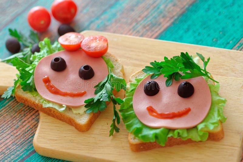 Fermez des sandwichs drôles les visages d'une fille et d'un garçon pour un repas scolaire Concept de nouveau ? l'?cole photos libres de droits