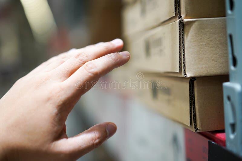 Fermez l'homme qui atteint sa main aux meubles dans une boîte de papier brune sur l'étagère dans l'entrepôt photographie stock libre de droits