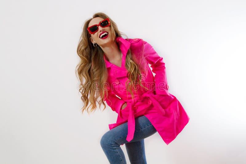Fermez la fille heureuse dans des lunettes de soleil rouges et un manteau rose isolé sur fond blanc excitée, choquante et surpris photo libre de droits