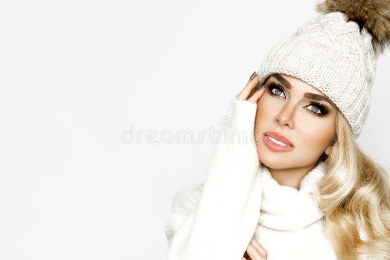 Fermez la photo d'une jeune fille de mode hivernale heureuse sur fond blanc Le mannequin porte un tricot blanc élégant photo libre de droits