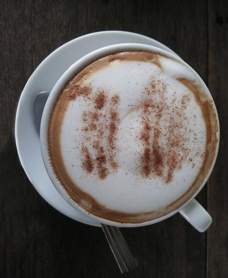 Fermez le cappuccino ou le latte avec de la mousse mousseuse dans une tasse de café blanche sur une table en bois noir dans le ca image libre de droits