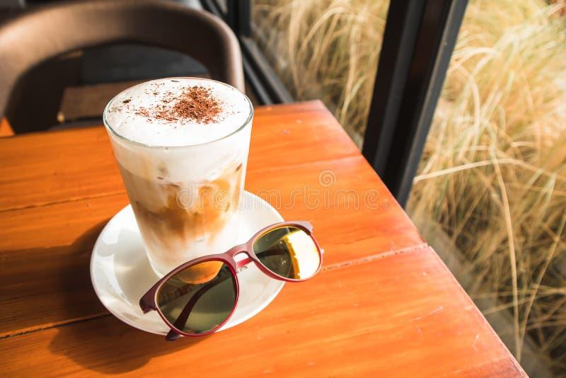 Fermez le verre de café glacé avec la poudre de chocolat, la mousse de lait et les lunettes de soleil photographie stock libre de droits