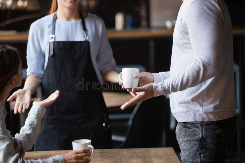 Fermez les clients indignés en se disputant avec la serveuse, le mauvais concept de service image stock
