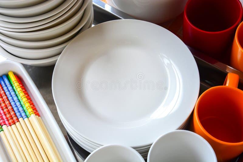 Fermez une pile de plats blancs vierges, de bols, d'assiettes, de tasses et de baguettes en bois colorés sur un plateau en métal photos libres de droits