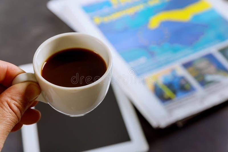Fermez vers le haut de la tasse de café d'expresso sur le journal la table photographie stock libre de droits