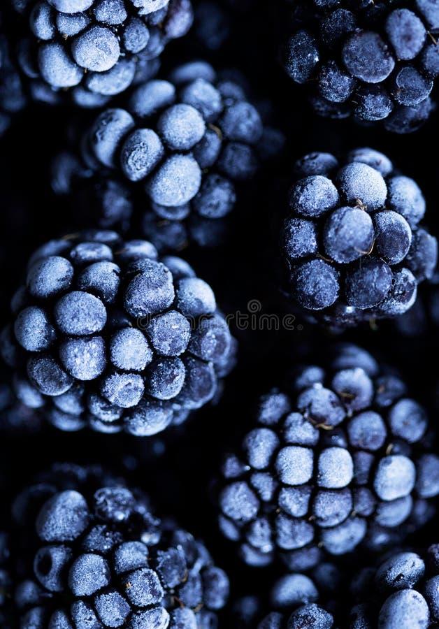 Fermez vers le haut de la vue sur les fruits surgelés de Blackberry une table en pierre noire Fond de nourriture photographie stock