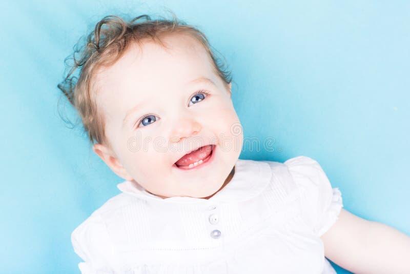 Fermez vers le haut du portrait du bébé bouclé dans les dres blancs image libre de droits