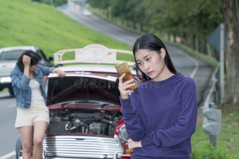 Fermez-vous à la jeune femme et à la voiture décomposée photo stock