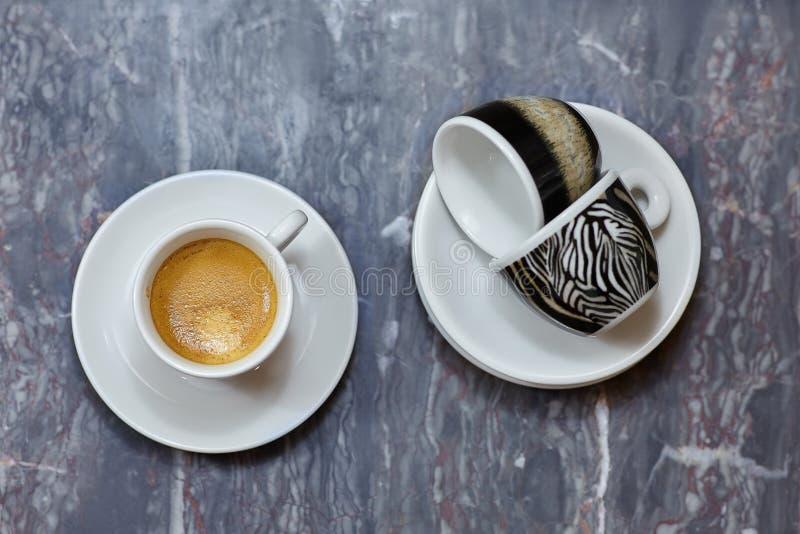Fermez-vous au-dessus de la vue de trois petites tasses et soucoupes, une avec l'expresso de café, deux que des autres sont vides photos stock