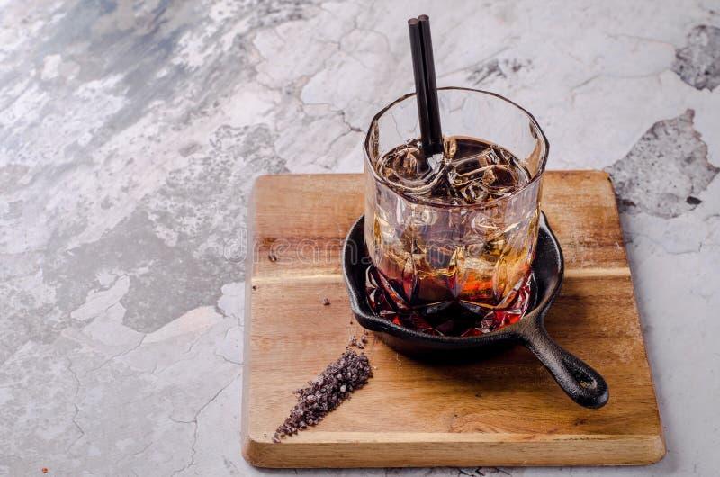 Fermez-vous, cocktail alcoolique brun avec le whiskey, décorations de glaçons sur un panneau en bois, fond gris Alcool de barre photos libres de droits