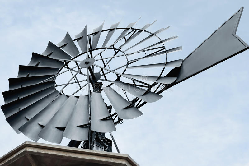 Fermez-vous d'a d'un moulin à vent de pompage de l'eau photographie stock