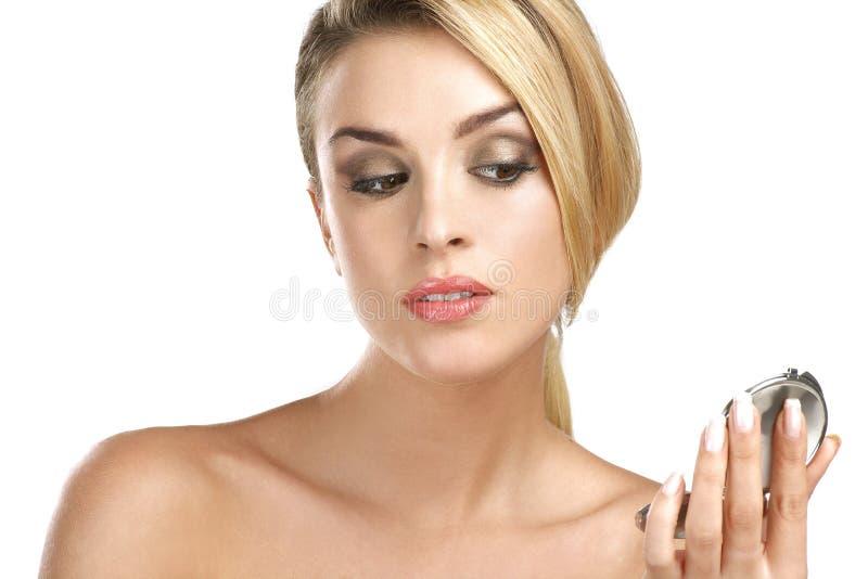 Fermez-vous d'a de jeune femme de beauté avec le miroir photographie stock libre de droits