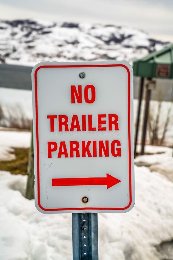 Fermez-vous d'un blanc et rouge aucun stationnement de remorque avec le signe de flèche en hiver photos stock