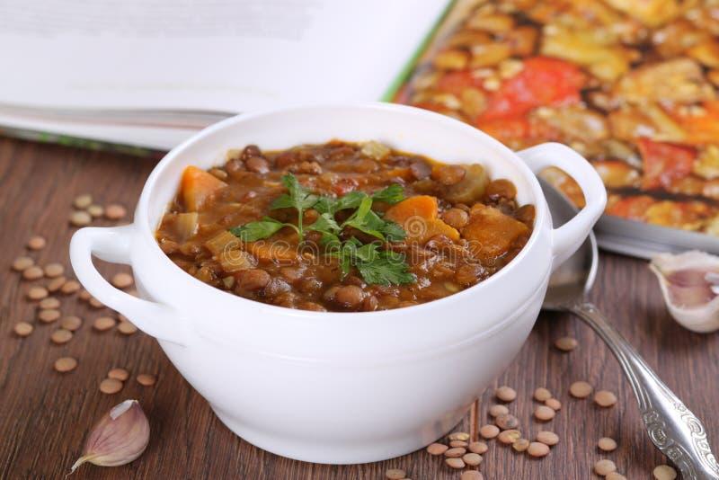 Fermez-vous d'un bol de soupe à lentille garni avec le persil photo stock