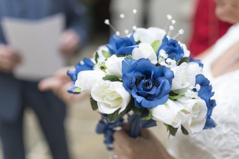 Fermez-vous d'un bouquet bleu et blanc de mariage tenu par la jeune mariée photo libre de droits