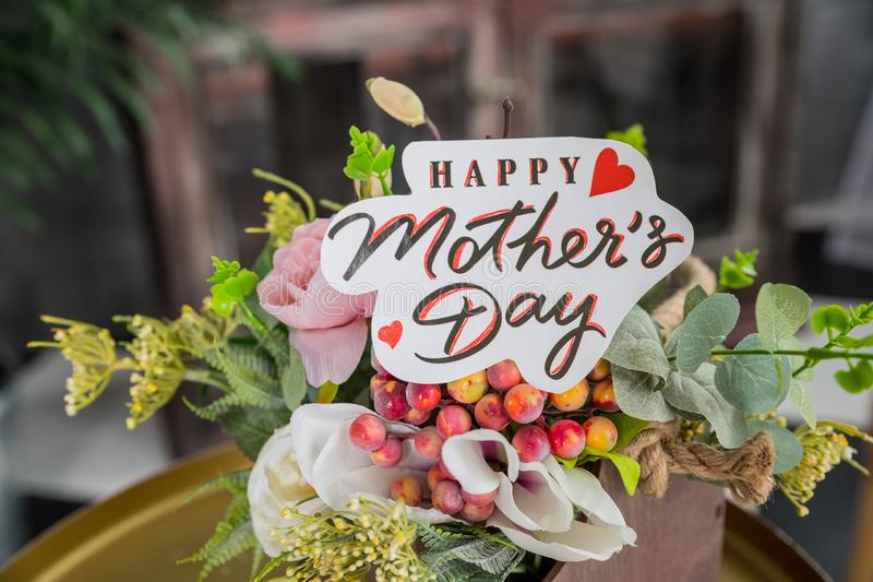 Fermez-vous d'un bouquet des roses roses avec une carte heureuse de jour de mères sur le fond brouillé Fond de jour du ` s de m?r photographie stock