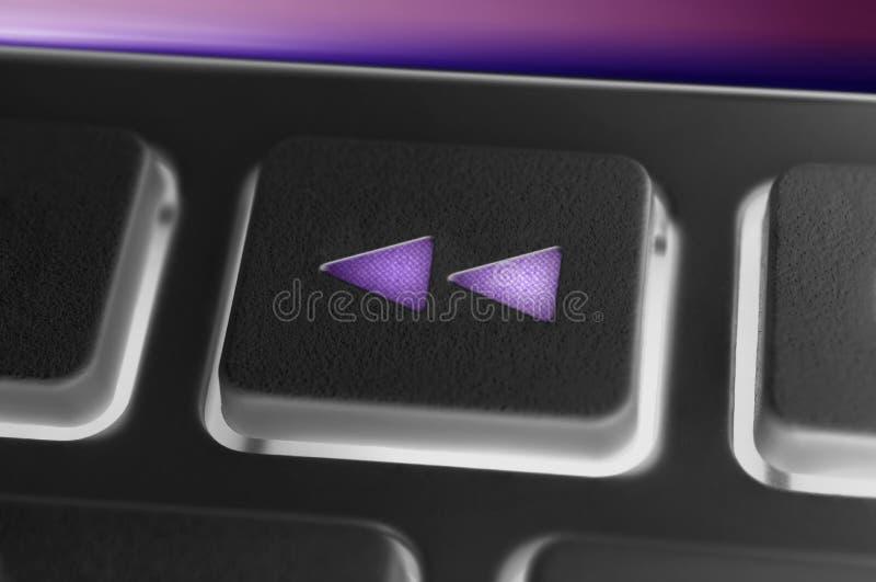 Fermez-vous d'un bouton de rebobinage noir d'un noir à télécommande avec le contre-jour image libre de droits