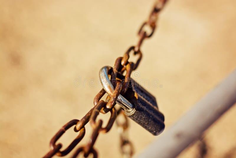 Fermez-vous d'un cadenas et d'une vieille chaîne rouillée sur un fond brouillé images stock