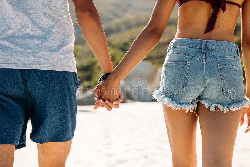 Fermez-vous d'un couple marchant en tenant des mains sur une plage photos libres de droits