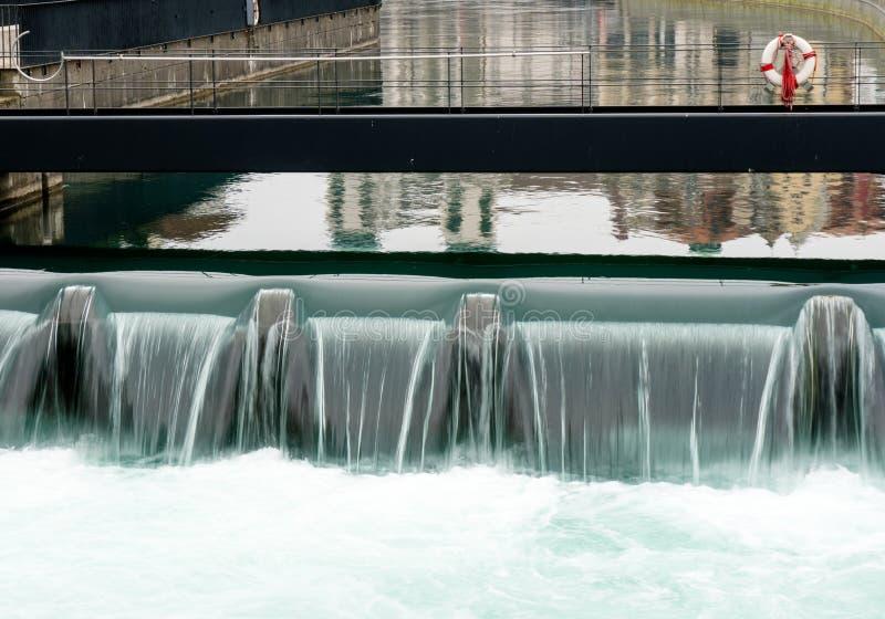 Fermez-vous d'un déversoir concret synthétique dans une ville avec une rivière bleue cascadant au-dessus de elle et une passerell photo stock
