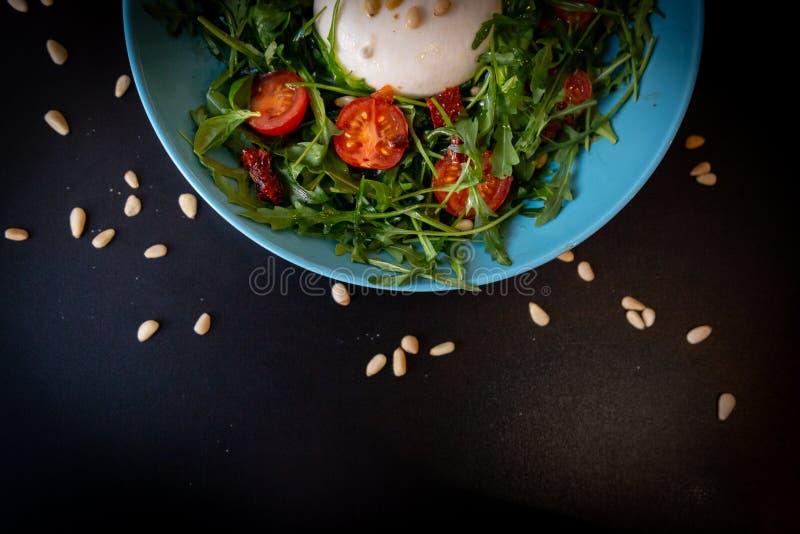 Fermez-vous d'un demi plat bleu de salade de fromage avec les tomates-cerises, l'arugula et les pignons sur une table noire photos stock
