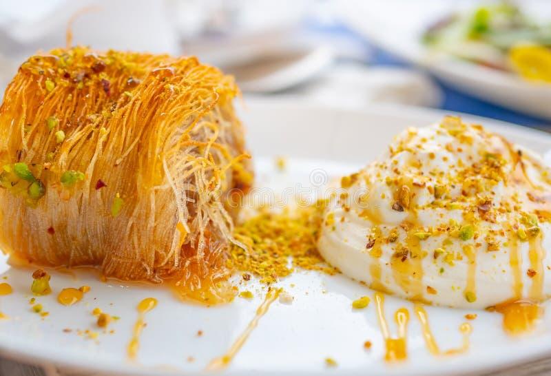 Fermez-vous d'un dessert grec succulent Kataifi grec avec du yaourt de miel et les pistaches râpées d'un plat et d'un blancs brou image stock