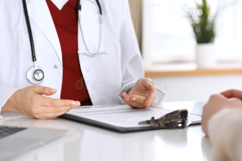Fermez-vous d'un docteur et des mains de patient tout en discutant les disques médicaux après examen de santé image libre de droits