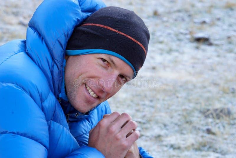 Fermez-vous d'un grimpeur de montagne masculin dans une veste épaisse de bas regardant plus d'et souriant photos stock