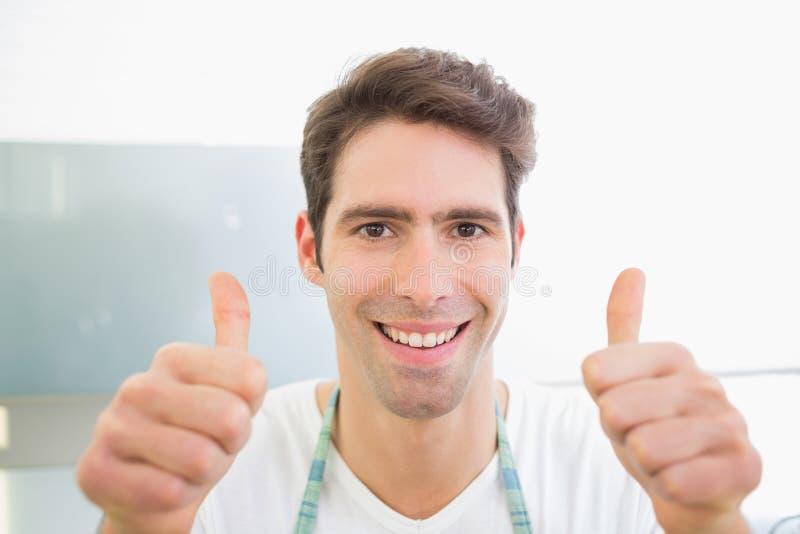 Fermez-vous d'un homme de sourire faisant des gestes des pouces  photos libres de droits