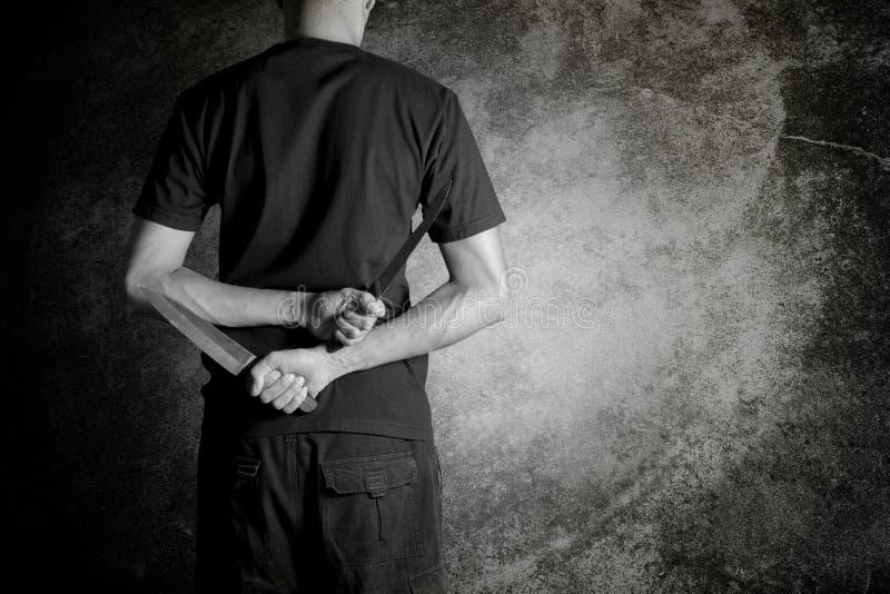 Fermez-vous d'un homme tenant le couteau derrière de retour contre le grunge noir photographie stock libre de droits