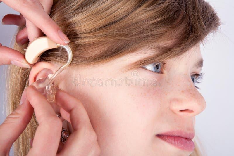 Fermez-vous d'un jeune girl& x27 ; tête et l'audiologist& x27 de s ; s remet l'inse photos libres de droits